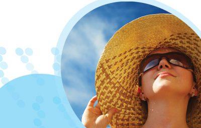 אישה עם כובע ומשקפי שמש מביטה בשמים