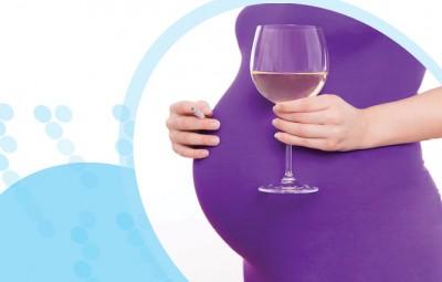 אישה בהריון מחזיקה כוס יין