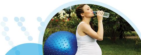 אישה בהריון שותה מים אחרי אימון