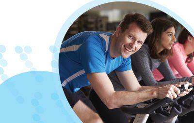 גבר ושתי נשים רוכבים על אופני כושר באימון ספינינג