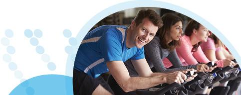 גבר ושתי נשים רוכבים על אופני כושר בשיעור ספינינג
