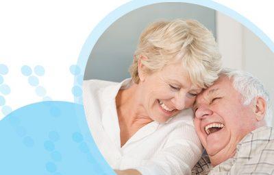 איש ואישה מבוגרים מחייכם וצוחקים ראש אל ראש