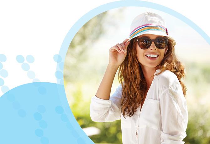 אישה עם שיער חום ארוך, מחייכת חובשת כובע ומרכיבה משקפי שמש