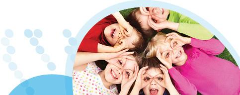 חמישה ילדים מחייכים שוכבים ראש אל ראש על הדשא, ומניחים ידיים על העיניים כמו משקפיים