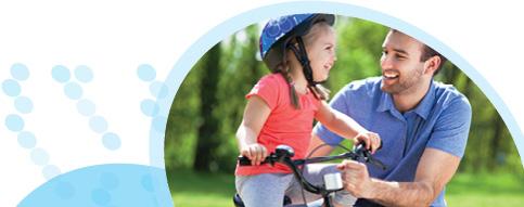 ילדה רוכבת על אופניים וחובשת קסדה כחולה ולצדה אביה שאוחז בכידון האופניים