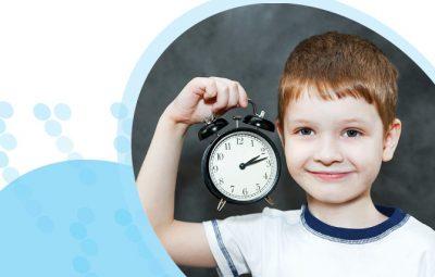 ילד מחייך מחזיק שעון מעורר ביד ימין ליד הראש