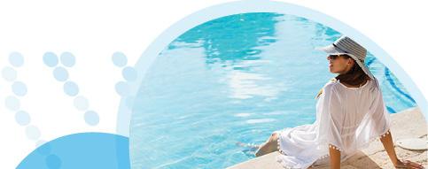 אישה עם כובע ובגדים לבנים יושבת על שפת הבריכה