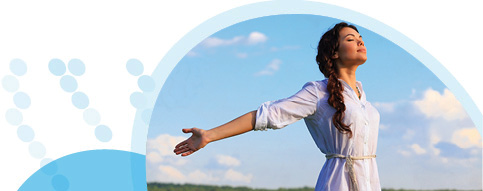 אישה לבושה לבן פושטת ידיים אחורה על רקע שדה ושמים כחולים