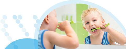פעוט מביט במראה ומצחצח שיניים