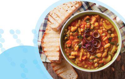 תבשיל קדירה עם ירקות וקטניות וצנימים על רקע מפה משובצת