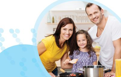 זוג הורים וילדה מבשלים יחד