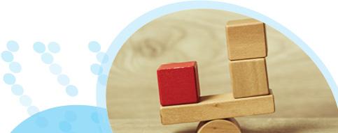 קוביות חומות ואדומות מאוזנות על קוביה חצי עגולה כבמאזניים