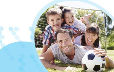אב אם ילד וילדה מחייכים נשענים זה על גבי זה ועל כדורגל על רקע שער ומגרש כדורגל